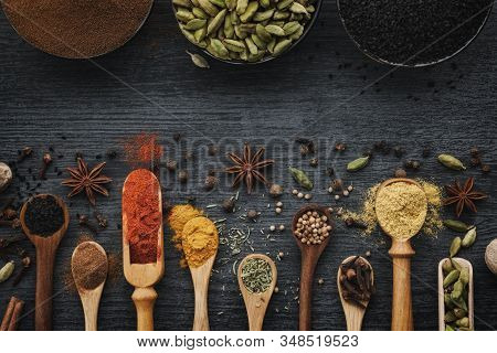 Various Aromatic Colorful Spices And Herbs In Wooden Spoons And Scoops. Black Ceramic Bowls Of Seaso