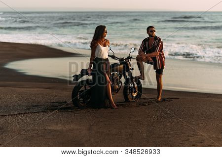 A Beautiful Couple On A Motorbike Meets The Sunset By The Sea. A Couple In Love On The Beach Meets T