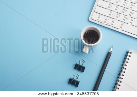 Blue Desk Office With Laptop, Smartphone And Other Work Supplies With Cup Of Coffee. Top View With C