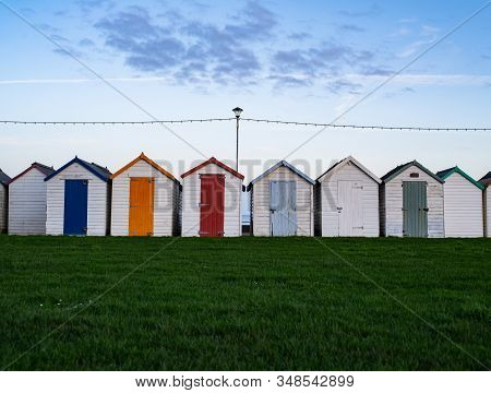 A Row Of Storage Sheds With Green Grass
