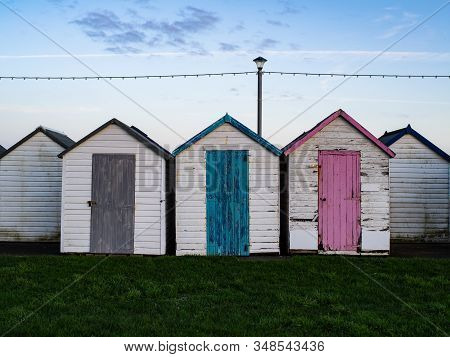 Three Colorful Storage Sheds In A Row With Green Grass