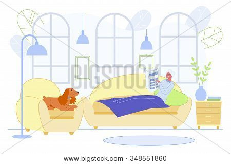 Relaxed Senior Lady Lying On Couch Under Warm Blanket Reading Newspaper In Living Room With Dog Sitt