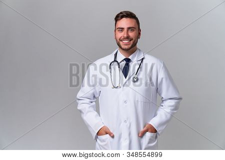 Young Handsome Modern Doctor White Medical Gown Stands In Studio Gray Background Student Trainee Of