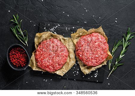 Home Handmade Raw Minced Beef Steak Burgers. Farm Organic Meat. Black Background. Top View