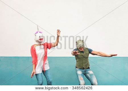 Happy Crazy Couple Dancing While Wearing T-rex And Unicorn Mask Outdoor - Seniors Having Fun Celebra