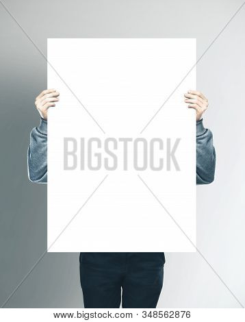 Businessman Holding Blank White Banner On Gray Background. Business Education Concept