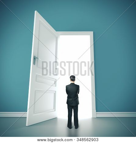 Businessman Standing In Blue Room With Open Doors. Success And Startup Concept.