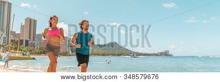 Runners couple running jogging on Hawaii Waikiki beach exercising outdoor in Honolulu city. Active lifestyle banner panoramic landscape background of healthy Asian girl, Caucasian man.