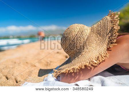 Beach suntan woman sleeping hiding under straw hat covering from sun lying down sunbathing on Caribbean travel vacation. Girl sleeping in shade.