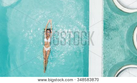 Woman relaxing in clear pool water in hot sunny day on Bali villa. Summer holiday idyllic, top view.
