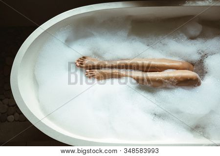 Woman relaxing with pleasue in foam bath with bubbles in modern hotel dark bathroom, slim legs with smooth skin closeup
