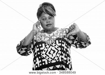 Portrait Of Stressed Overweight African Woman Talking On The Phone And Giving Thumbs Down