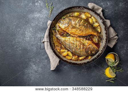 Baked Sea Bream Or Dorada With Onion And Herbs In Pan On Dark Background