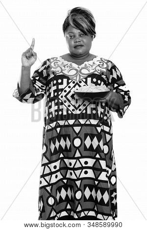 Overweight African Woman Holding Bowl Of Potato Chips And Pointing Finger Up