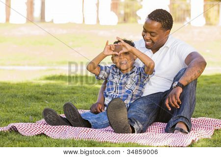 Happy African American Father and Mixed Race Son Making Heart Hand Sign at the Park.