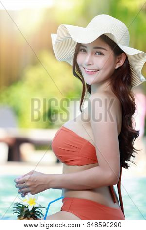 Beautiful Female In Bikini Relaxing At The Pool With Cocktail.