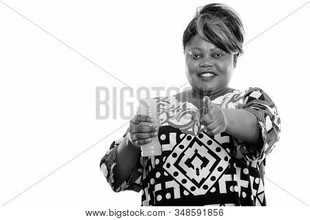 Happy Overweight African Woman With Bottle Of Orange Juice Giving Thumbs Up