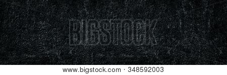Old Black Textured Plaster Wide Surface. Rough Cement Wall Widescreen Backdrop. Dark Gloomy Abstract