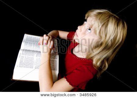 Little Girl Praying Over Bible