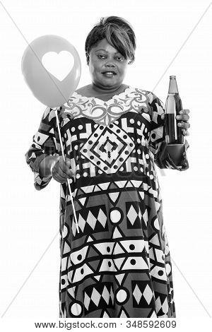 Happy Overweight African Woman Standing While Holding Balloon With Heart Sign And Bottle Of Beer