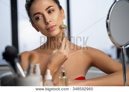 Lovely Calm Female Holding A Face Massager
