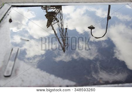 Urban Reflection: A Lighting Pole, A Crane And A Sky With Clouds Reflected On The Surface Of The Wat