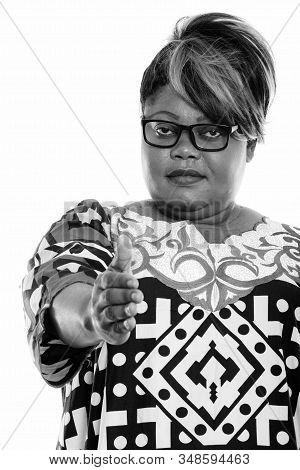 Studio Shot Of Fat Black African Woman Wearing Eyeglasses While Giving Handshake