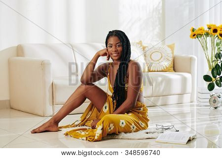 Portrait Of Beautiful Attractive Young Woman Sitting On The Floor In Living Room And Smiling At Came