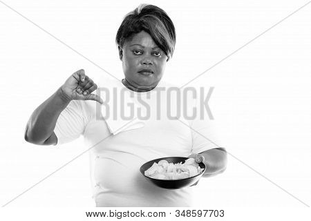 Studio Shot Of Fat Black African Woman Holding Bowl Of Potato Chips And Giving Thumb Down