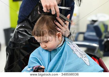 Haircut Boy 0-1 Years. The First Haircut Of The Child At The Hairdresser. Baby Haircut Toddler.