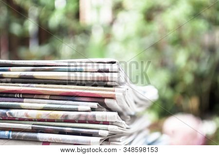 Newspapers Folded And Stacked On The Table With Garden Or Green Background. Closeup Newspaper And Se