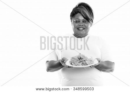 Studio Shot Of Happy Fat Black African Woman Smiling While Holding Lettuce Served On White Plate