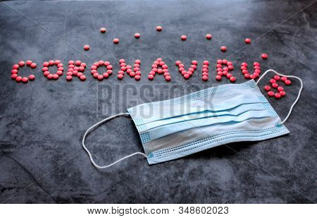 Respiratory Protection Medical Mask Next To The Word Coronavirus Laid With Red Pills On Dark Backgro