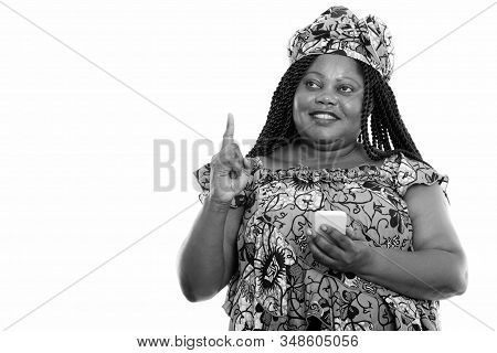 Happy Overweight African Woman With Traditional Clothes Thinking And Pointing Up While Using Phone
