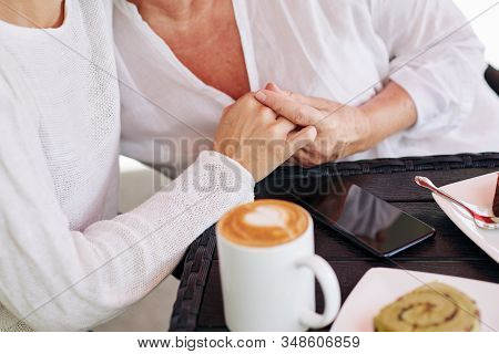 Close-up Image Of Daughter Reassuring Her Mother And Holding Her Hand When They Are Drinking Coffee