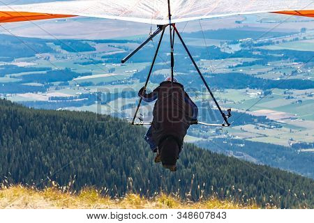 Professional Hang Glider Man Taking Off From The Mountain Top. Hang Gliding In Action. Soaring Fligh
