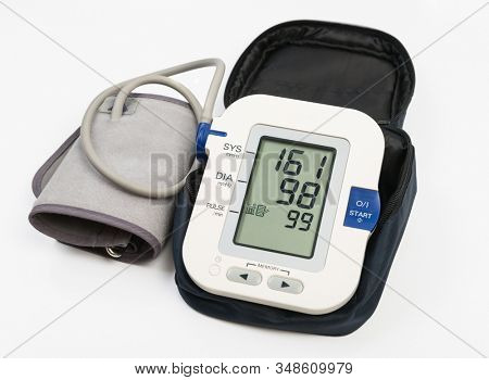 Electronic blood pressure meter and cuff in case. Meter display showing high blood pressure 151/98. Clipping path