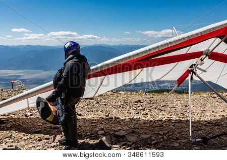 Professional Pilot Standing Near With His Hang Gliders And Getting Ready To Fly. Extremal And Risky