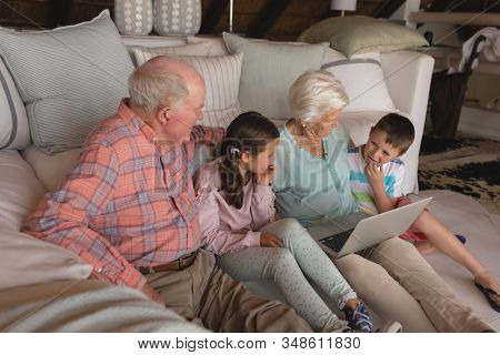 Front view of a multi-generation family using laptop on the floor of the living room at home