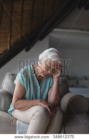 Front view of a worried senior woman sitting on sofa and holding her head in living room at home