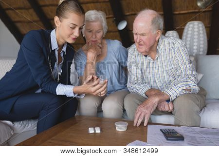 Front view of a female doctor and senior couple looking and discussing over medicine they hold in their hands at home