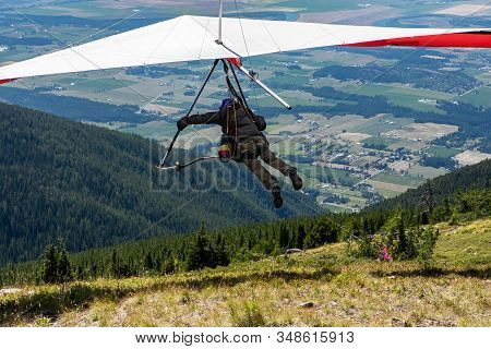 Rearview Of Hang Gliding Young Man Over Farmlands And Mountains In Creston, British Columbia, Canada