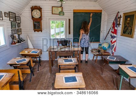 Young Woman Writing On The Chalkboard. An Old British Class Of The 20th. Real School Class Of The 19
