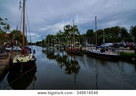 Edam, The Netherlands, August 2019. In The Historic Center The Canal With Moored Boats. The Crowns O