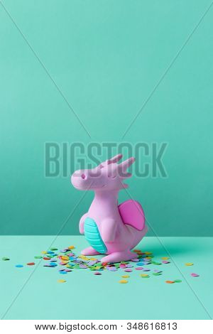 Cute rubber dinosaur toy on green background.