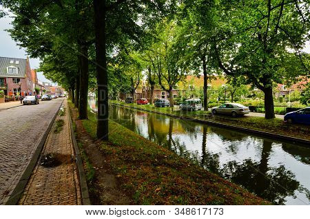 Edam, The Netherlands, August 2019. One Of The Pretty Canals Of This Town: The Foliage Of The Trees