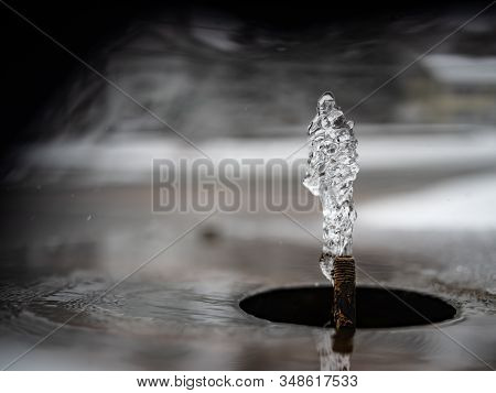 Water Erupts From A Small Spigot With A Beautiful Background