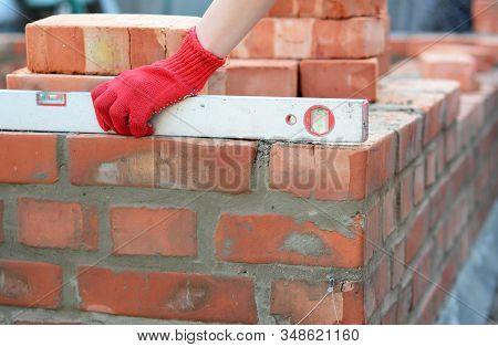 Spirit Levels For Bricklaying. Bricklayer Girl Hand Using A Spirit Level To Check Bricklaying Founda
