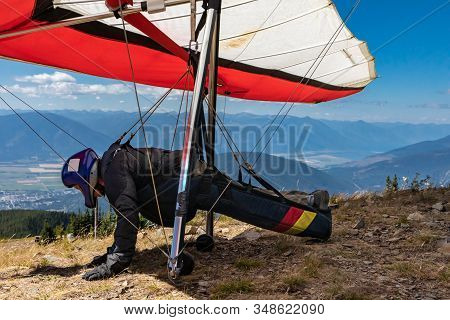 Man With Hang-glider Getting Ready To Fly From The Top Of Mountain Hill. Para Glider Pilot Getting R