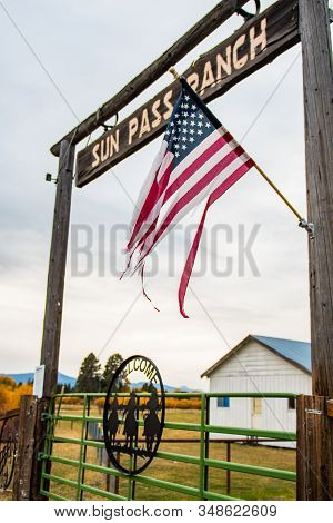 Fort Klamath, Oregon, Usa - October 23, 2018: A Tattered U.s. Flag And Wooden Archway At The Entranc
